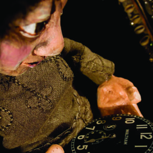 Close-up of puppet staring at a the hands of a pocket watch