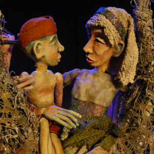 Close-up of mother and son puppets sitting in a tree