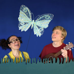 girl and boy looking up in delight at butterfly puppet