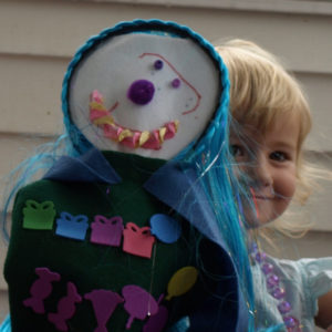 Smiling child plays with a hand puppet she's made